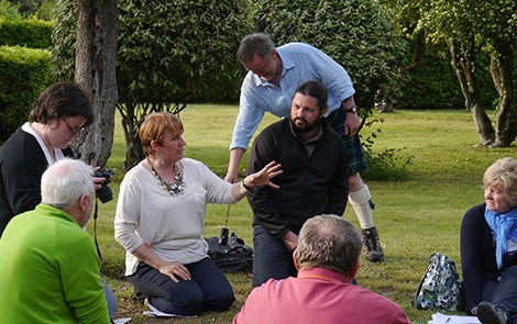 A group of 6 people sat on the lawn at the Italian President's summer residence, participating in a workshop for Interpret Europe, being led by Susan Cross. One man in a kilt is stood in the background putting a camera on the ground.