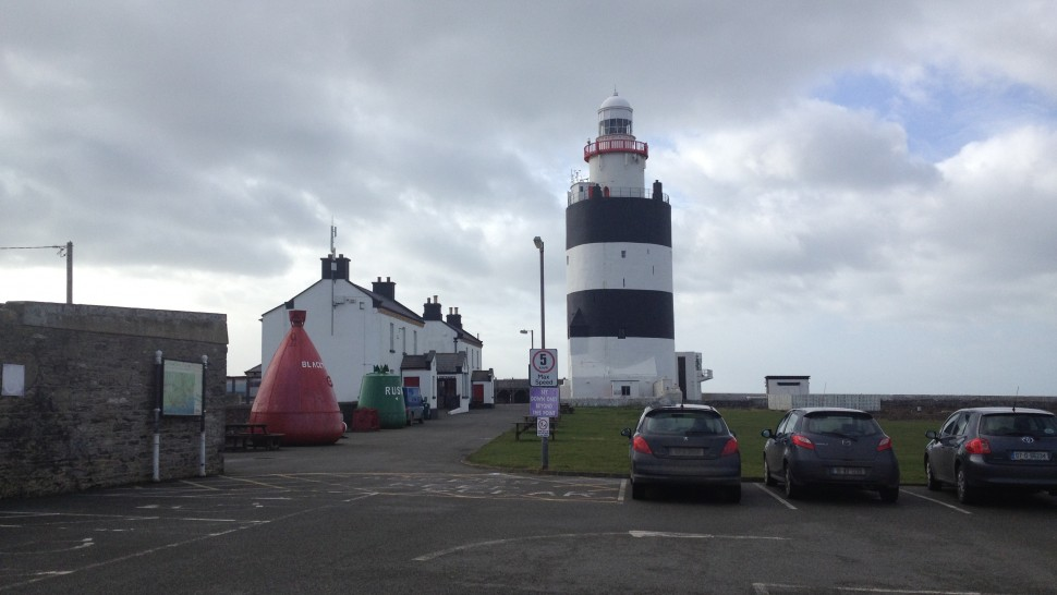 Hook Lighthouse, which is black and white, next to a row of three white houses and a car park