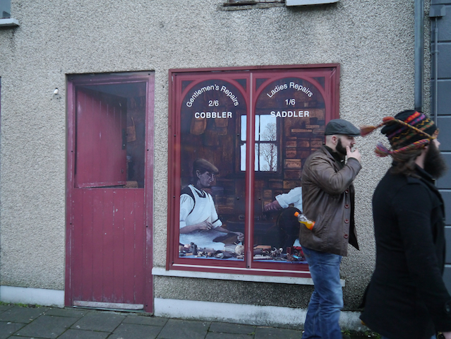 A shop door and window in Bushmills, Northern Ireland. The door is half open and slightly tatty and this is a painting. The shop window is also a painting showing a cobbler and a saddler at work.