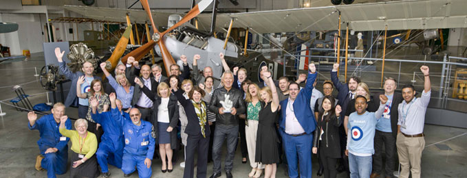 Staff and volunteers of the Royal Air Force Museum celebrating their win with Martin Kemp, crowded around a plane