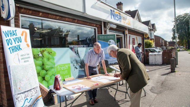 An older man writing down his views during an audience consultation outside a supermarket in Bedfordshire