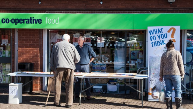 An older man giving his feedback during an audience consultation outside a supermarket in Bedfordshire
