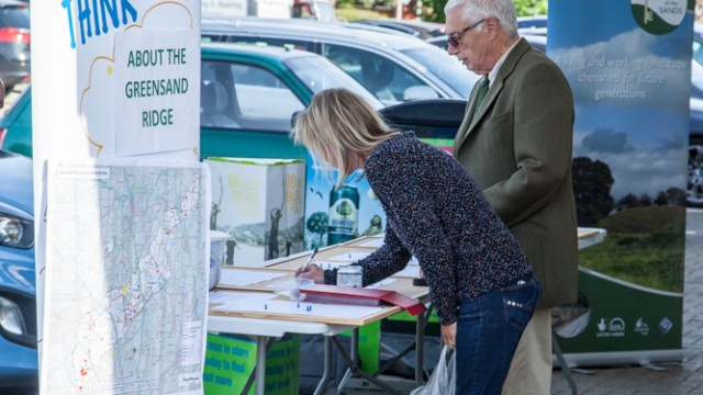 Two people (a middle aged woman and an older man) giving their views at audience consultations outside a supermarket in Bedfordshire