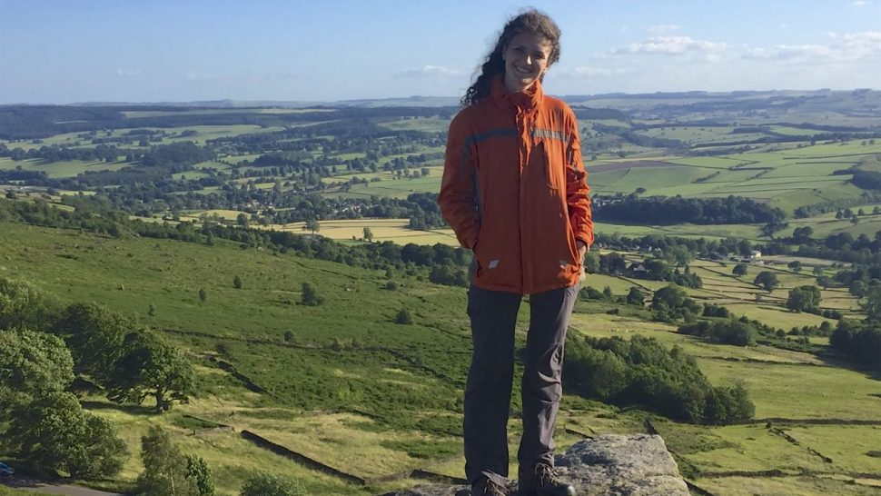 Karolina standing on a rocky outcrop with views over the Peak District stretching into the far distance
