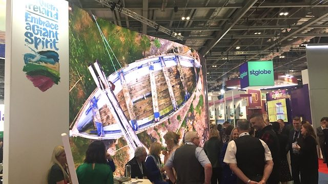 Exhibition hall stand. A large photograph of a rowing boat and the Embrace a Giant Spirit logo. Crowds of people